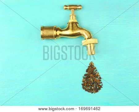 Faucet with water drop made of rust flakes on color wooden background