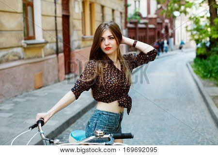 Portrait of attractive girl with perfect slim body holding bicycle handlebar wearing denim shorts and shirt. On the street background.