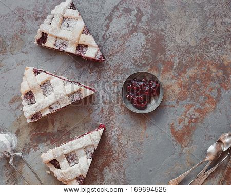 Cranberry pie slice with lattice top and  jellied fresh cranberries. Top view, vintage toned image, blank space