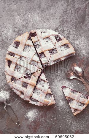 Lattice top cherry pie with powdered sugar on rustic table. Top view, blank space, vintage toned image