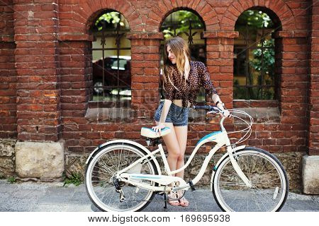 Happy girl with long fair hair wearing on dark blouse and  blue shorts standing with bicycle near the brick building, on the old city street