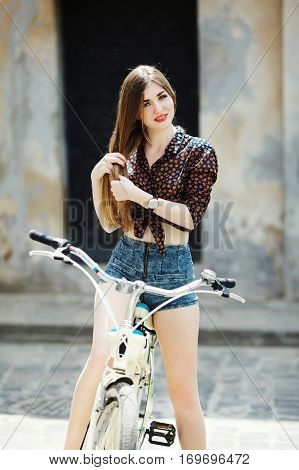 Pretty young girl wearing on dark blouse and blue shorts with long straight fair hair is sitting on bicycle and looking at camera on the street of old European city.