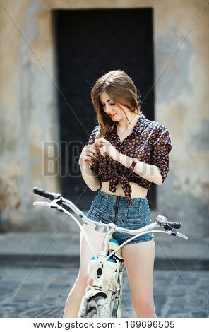 Attractive young girl wearing on dark blouse and blue shorts with long straight fair hair sitting on the bicycle on the street of old European city.