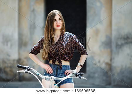 Young nice girl wearing on dark blouse and blue shorts with long straight fair hair is posing on the bicycle on the street of old European city.