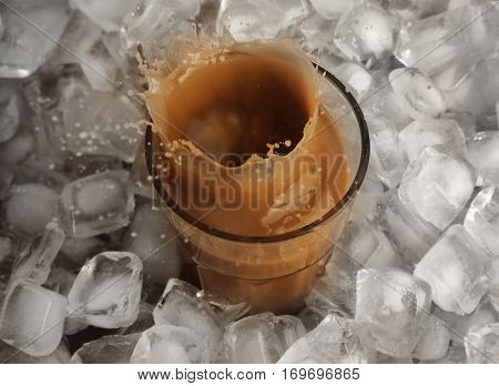 Glass of cold coffee with ice cubes and splashes on table