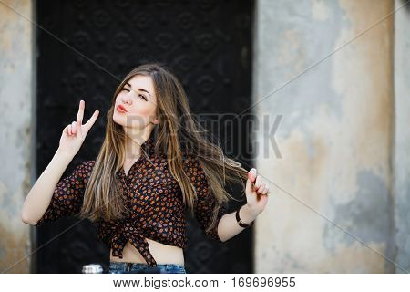 Positive cute girl with long straight fair hair wearing on dark blouse is posing on the bicycle on the street of old European city