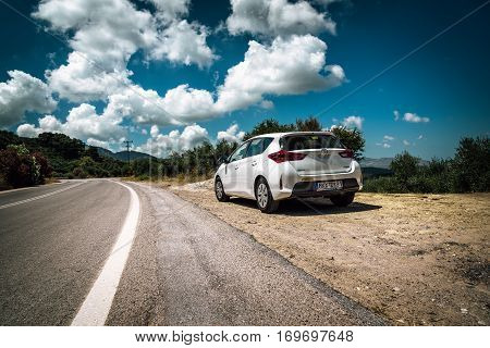 PALEOCHORA, CRETE, GRECE - AUGUST 2016: White Toyota Auris stays parked among clouds on road of Crete island. The Toyota Auris is a compact hatchback