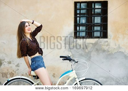 Pretty girl with long fair hair wearing on dark blouse and blue shorts is sitting on the bicycle and have fun on the old wall background.