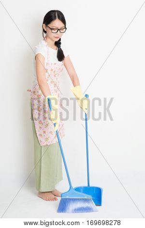 Young Asian woman sweeping floor with broom and dustpan , cleaning floor.
