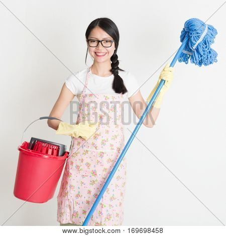 Young Asian housewife hand holding bucket and mop, doing house chores.