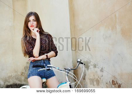 Nice girl with long straight fair hair wearing on dark blouse and blue shorts is posing on the bicycle on the old wall background in the European city.
