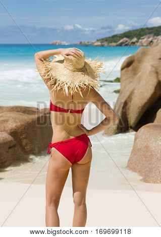 Slender woman in straw hat, red swimsuit, beach in Seychelles
