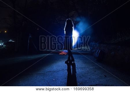 blue backlight girl silhouette in the street night