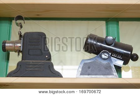 Old two objects like microscope on the shelf