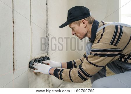 Installing electrical socket box. The electrician attaches to the wall socket box using gypsum plaster.