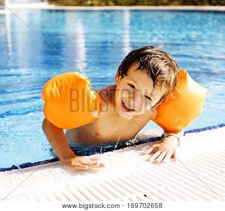 little cute boy in swimming pool wearing orange handcarves