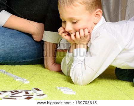 child with his mother playing dominoes lying on the carpet