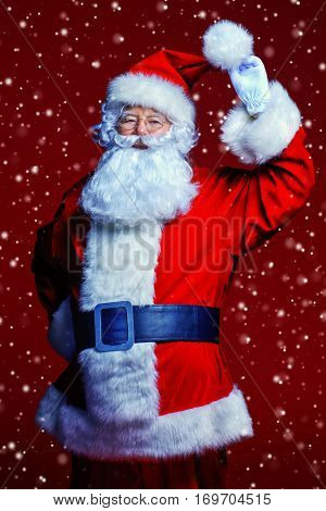 Christmas and New Year concept. Santa Claus holds his hat. Red background.