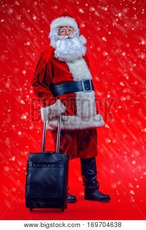 Christmas, tourist trip concept. Santa Claus with suitcase is going to travel around the planet. Christmas time. Time for miracles. Copy space.