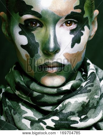 Beautiful young fashion woman with military style clothing and face paint make-up, khaki colors green