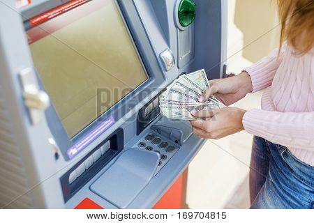 Repayment on credit. Woman hand withdrawing money from outdoor bank ATM
