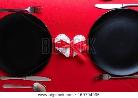 White heart with red ribbon bow between two dish plates on Valentine's Day. Romantic dinner setting for two abstract concept. Flat lay top view.