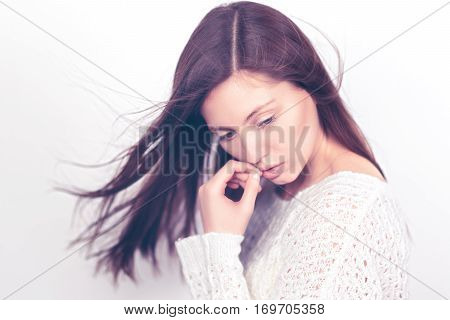Beautiful young girl on a light background. Fashionable young woman. Without makeup. Spring photo. Toned image.