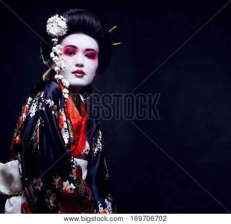 young pretty geisha in kimono with sakura and decoration close up