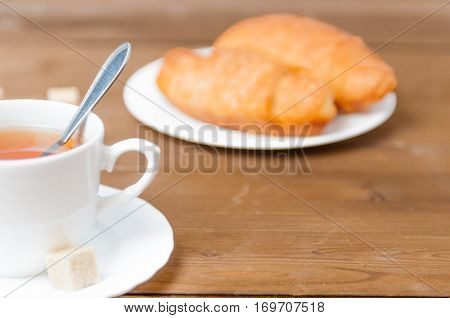 Fresh breakfast with cup of tea and a croissant. Festive breakfast Valentine's Day with love. Tasty and healthy breakfast. Shallow depth of field. Close up.