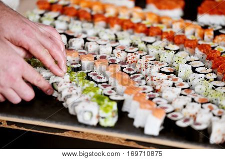 Hands arranging different sushi appetizers on a plate