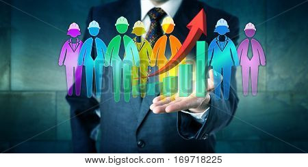 Business man holding a group of worker icons and an exponential growth trend graph in the open palm of his left hand. Concept for multi-ethnic teamwork service solution and motivation management.