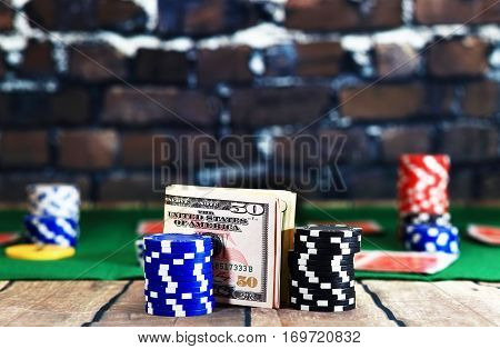 Close up of money between casino chips on poker play background. Dollars on wooden table on brick wall background. Online casino background.