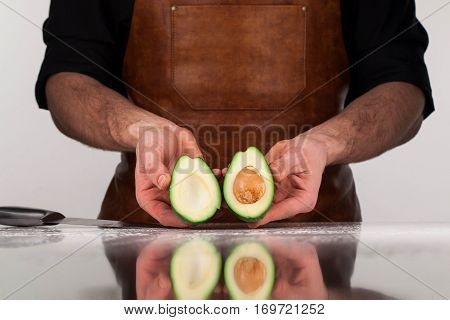 Avocado halves in chef's hands. White background