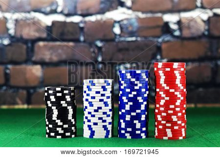 Columns of poker chips on green poker table. Close up color  chips on brick background. Perfect online games concept