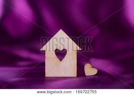 Wooden House With Hole In Form Of Heart On Crimson Satin Fabric