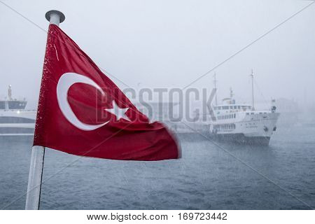 ISTANBUL TURKEY - DECEMBER 30 2015: Turkish flag during a snowstorm a Europe-Asia ferryboat can be seen in the background