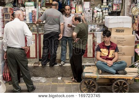 TEHRAN IRAN - AUGUST 14 2016: Merchants and delivery boys having a break and discussing in a covered street of Tehran bazaar