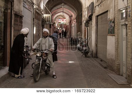 YAZD IRAN - AUGUST 18 2016: Iranian Imams wearing traditional clothes discussing while on a motorbike in a covered street of Yazd Bazaar