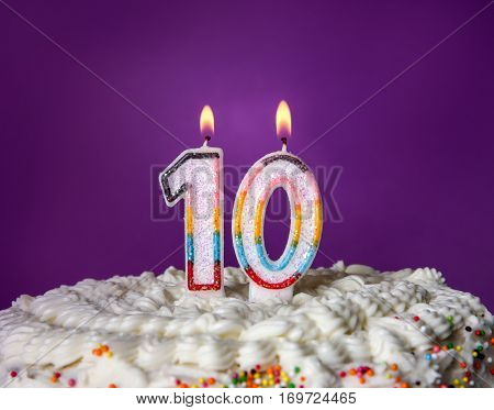 Tasty cake with candles for tenth birthday on purple background