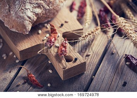 Fresh multigrain crusty bread chilly pepper and wheat ears on a rustic wooden table. Bakery and grocery food store concept.