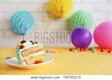 Saucer with piece of Birthday cake and decor on brick wall background
