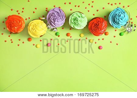 Tasty cupcakes and sweet balls on green background, top view