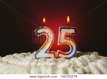 Tasty cake with candles for twenty fifth birthday on purple background