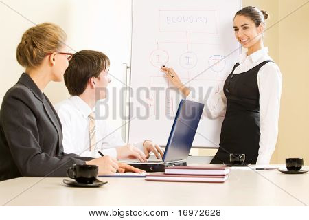 Photo of successful manager standing by whiteboard while her colleagues listening to her