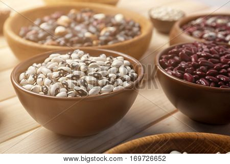 Assortment of haricot beans in bowls on wooden background