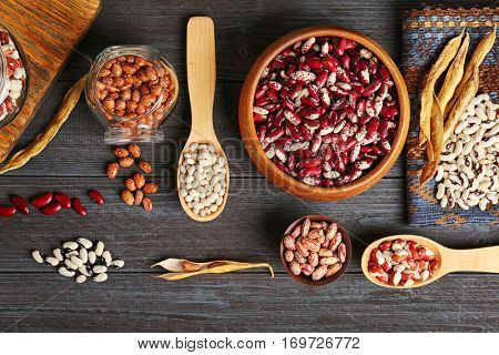 Assortment of haricot beans in bowls and spoons on dark wooden background