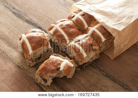 Hot Cross Buns for Easter in a brown paper packet spilling out onto a wooden table with one bun having a missing bite