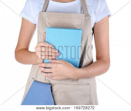 Woman in apron holding cookbook on white background, closeup