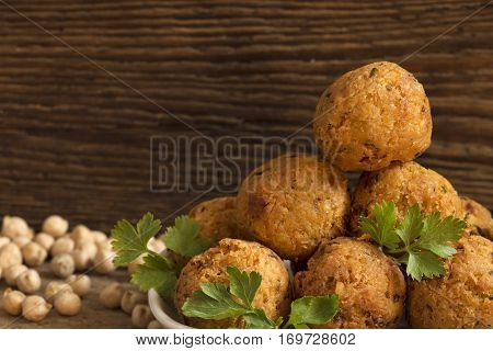 Falafel balls with parsley on wooden background