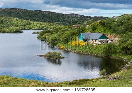 Assynt Peninsula Scotland - June 7 2012: Cottage under construction at charming small lake with multiple green islands at Drumbeg hamlet. Blue sky green hills blue water green pasture.